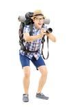Männlicher Tourist mit dem Rucksack, der ein Foto mit der Kamera macht Stockbild
