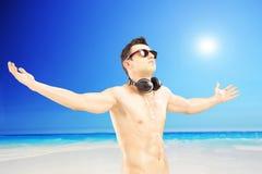 Männlicher Tourist mit den Speakerphones, die seine Arme, nahe bei einem Se verbreiten Lizenzfreies Stockbild