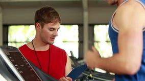 Männlicher Trainer, der über Tretmühlenleistung schreibt stock video