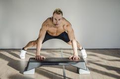 Männlicher Trainer junger Aerobic auf unterrichtender Klasse des Schrittes Stockfotografie