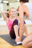 Männlicher Trainer mit Frau, die das Handeln sitzt, ups in die Turnhalle Stockfotografie