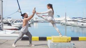 Männlicher Trainer, welche der jungen Frau trainiert auf Pier hilft stock footage