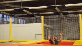 Männlicher Turner, der auf eine Trampoline springt stock video footage