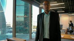 Männlicher Unternehmer des jungen Afroamerikaners, der auf Gläser sich setzt und Kamera betrachtet stock video footage