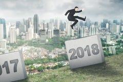 Männlicher Unternehmer springt zwischen Zahlen 2017 und 2018 Stockfotos