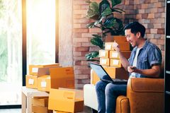 Männlicher Unternehmer unter Verwendung des Laptops mit Sätzen Kästen zu Hause mit Aufregung lizenzfreie stockfotos