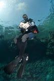 Männlicher Unterwasseratemgerättaucher, der eine Oberflächenboje anhält. lizenzfreie stockfotos