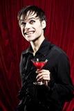 Männlicher Vampir mit einem blutigen Getränk Stockfotos