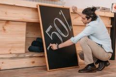 Männlicher Verkäufer, der fünfzig-Prozent-Rabattzeichen auf Tafel zeichnet Lizenzfreies Stockbild