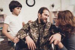 Männlicher Veteran im Rollstuhl-Heimkehr-Konzept stockfoto