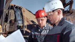 M?nnlicher Vorarbeiter und Arbeitskraft im Sturzhelm und Gl?ser, die den Bauplan schaut auf Zeichnung besprechen stock footage