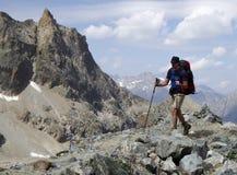 Männlicher Wanderer auf einem felsigen und staubigen Wanderweg in den französischen Alpen Lizenzfreie Stockfotos