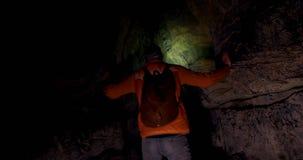 Männlicher Wanderer, der eine dunkle Höhle 4k erforscht stock video footage