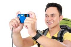 Männlicher Wanderer mit Rucksack unter Verwendung des Handys Stockfoto