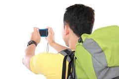 Männlicher Wanderer mit Rucksack unter Verwendung des Handys Stockbild