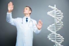 Männlicher Wissenschaftler, der Genetik über Hintergrund studiert stockfoto