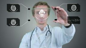Männlicher Wissenschaftler, der Röntgenstrahl, Tomogramm auf einer futuristischen Tablette analysiert Bewegungsgraphik stock video footage