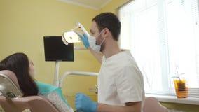 Männlicher Zahnarzt bereitet für den Bericht einen weiblichen Patienten in der zahnmedizinischen Klinik vor stock video footage