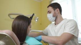 Männlicher Zahnarzt bereitet vor sich, einen weiblichen Patienten in der zahnmedizinischen Klinik zu überprüfen, setzt an sterile stock footage