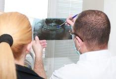 Männlicher Zahnarzt, der die Details eines Röntgenstrahlbildes seinem PA erklärt Stockbild