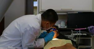 Männlicher Zahnarzt, der einen Patienten mit Werkzeugen 4k überprüft stock footage