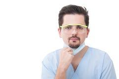 Männlicher Zahnarzt, der seine Schutzmaske hält Lizenzfreies Stockfoto