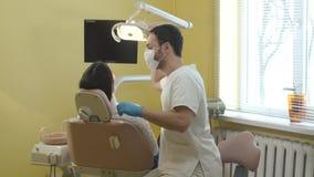 Männlicher Zahnarzt mit Maske auf dem Gesicht sprechend mit einem weiblichen Patienten vor dem Verfahren stock video footage