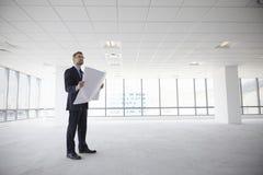 Männliches Architekten-In Modern Empty-Büro, das Pläne betrachtet lizenzfreie stockfotografie