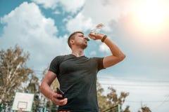 Männliches Athletenläufer-, Stillstehen und Trinkwasser von einer Wasserflasche In seiner Hand pulsieren Telefonkontrollen, Anwen stockfotografie