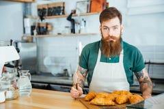 Männliches barista mit Bart und die Tätowierung, die im coffe steht, kaufen Stockbild