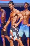 Männliches Eignungsmodell zeigt seine Konstitution in Badeanzug-OM-Stadium Stockfotos