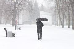 Männliches Fußgängerverstecken vom Schnee unter Regenschirm Stockfoto