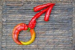 Männliches Geschlechtssymbol gelegt mit Cayenne-Pfeffern Lizenzfreies Stockfoto