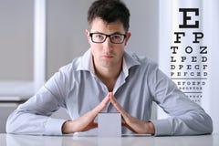 Männliches Gesicht mit Schauspielen auf Sehvermögentestseitehintergrund Stockfotos