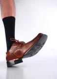 Männliches haariges Fahrwerkbein mit schwarzer Socke und braunem Schuh. Stockbild