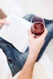 Männliches Hand-holdind Buch und Glas Rotwein Stockbilder