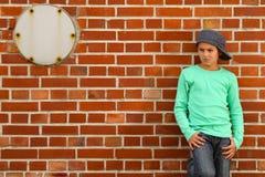 Männliches Kind, das auf einer Ziegelsteinsteinwand steht Stockbild