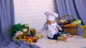 Männliches Kind des entzückenden Babys im Küchenkochen, spielend mit Bank von Linsen stock video
