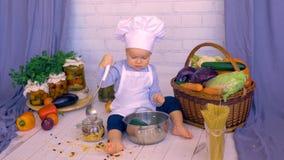 Männliches Kind des entzückenden Babys im Küchenkochen, spielend mit Bank von Linsen stock video footage