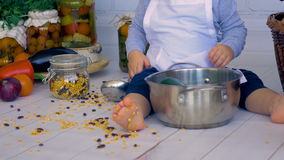Männliches Kind des entzückenden Babys im Küchenkochen, spielend mit Bank von Linsen stock footage
