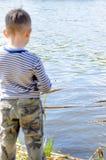 Männliches Kind am Flussufer, der für die Fischerei sich vorbereitet Lizenzfreies Stockbild