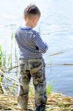 Männliches Kind am Flussufer, der für die Fischerei sich vorbereitet Lizenzfreies Stockfoto