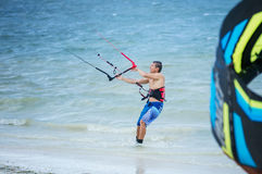 Männliches kitesurfer, das oben dem Drachen betrachtet lizenzfreie stockbilder