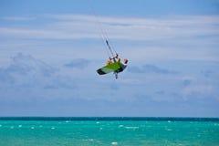 Männliches Kitesurfer, das seinen Vorstand grabing ist Lizenzfreie Stockbilder