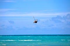 Männliches Kitesurfer, das seinen Vorstand grabing ist Lizenzfreies Stockbild