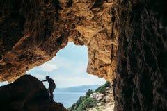 Männliches Klettererschattenbild auf einer Klippe in einer Höhle stockfoto