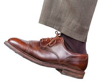 Männliches linkes Bein im braunen Schuh unternimmt einen Schritt Lizenzfreies Stockbild