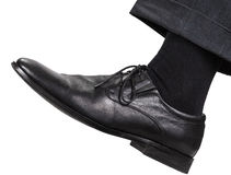 Männliches linkes Bein im schwarzen Schuh unternimmt einen Schritt Stockfotos