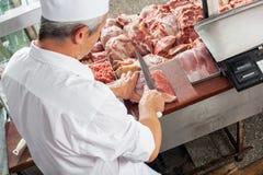Männliches Metzger-Cutting Meat At-Verkaufsmöbel Stockbild