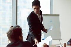 Männliches Mitteilungsblattmaterial des Angestellten Anteiles zu den Kollegen bei der Sitzung lizenzfreie stockbilder